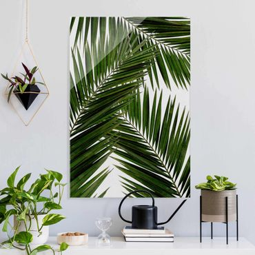 Glasbild - Blick durch grüne Palmenblätter - Hochformat