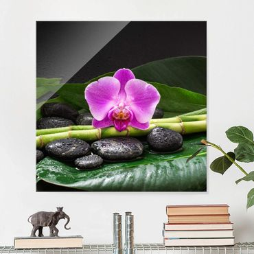Glasbild - Grüner Bambus mit Orchideenblüte - Quadrat 1:1