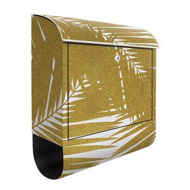 Briefkasten - Blick durch goldene Palmenblätter